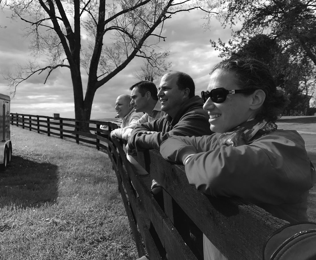 CLD Partners team members posing on fence on a ranch