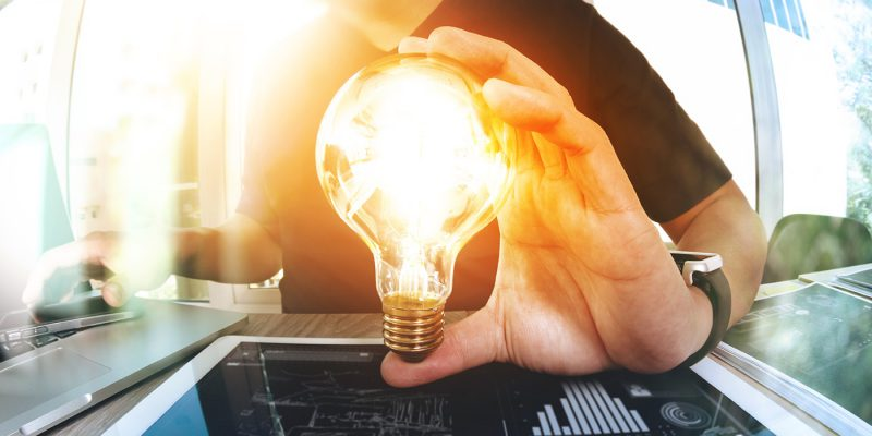 Person holding a lightbulb turned on because its a bright idea to transition FinancialForce to LEX