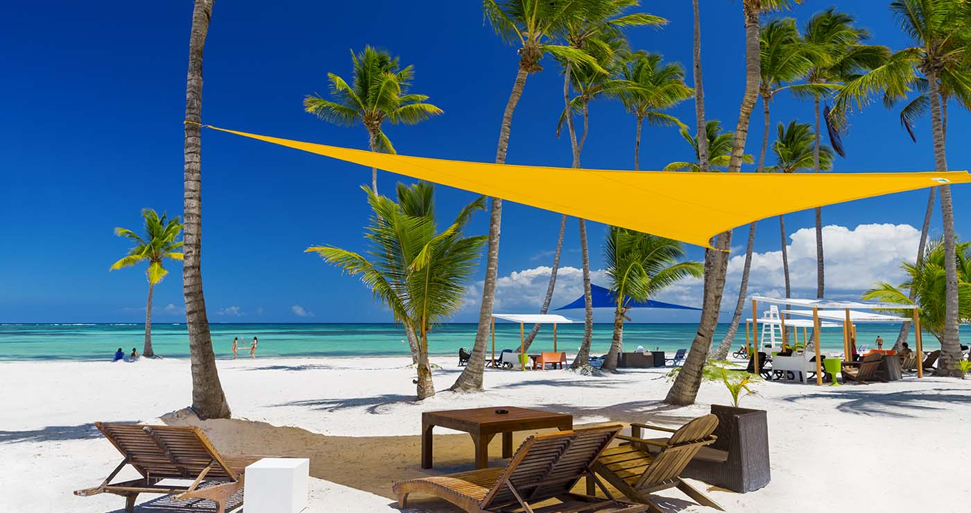 beach with palm tress in the tropics with wooden beach chairs under a shade sail