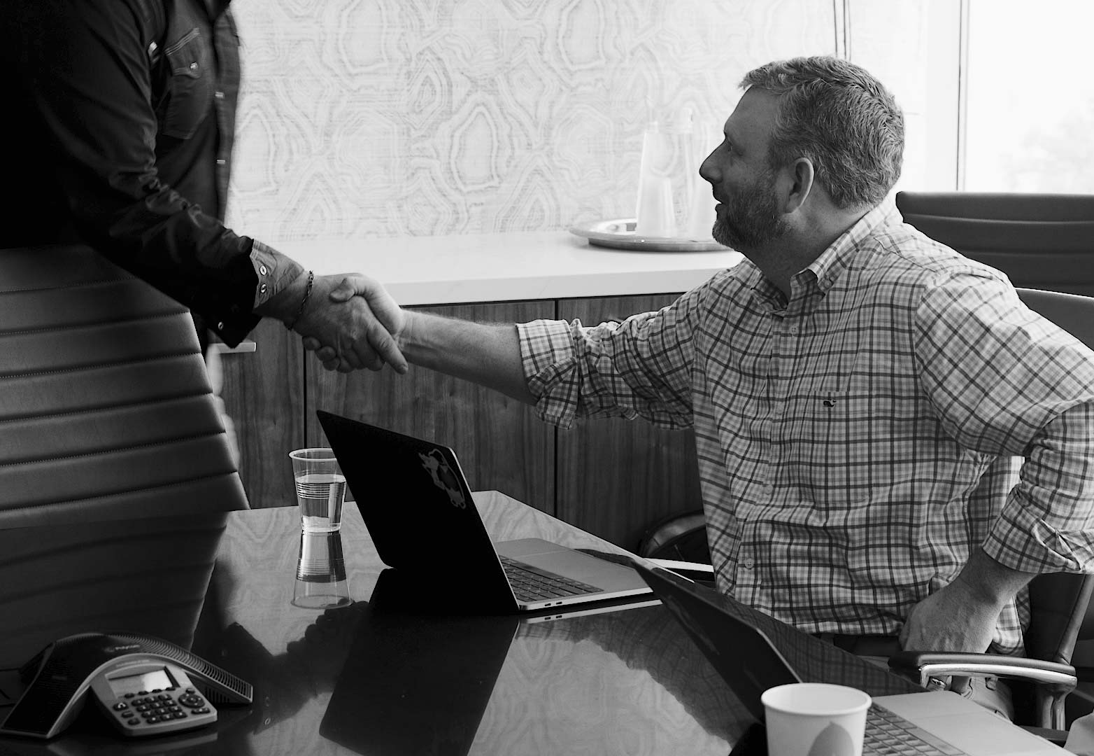 two men shaking hands at a meeting about financialforce implementation services