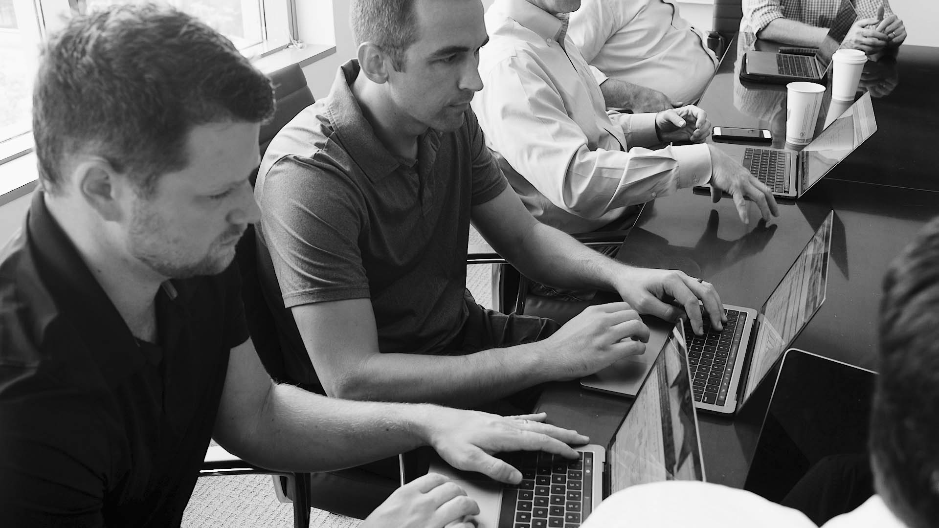 two FinancialForce services team members looking at their laptops