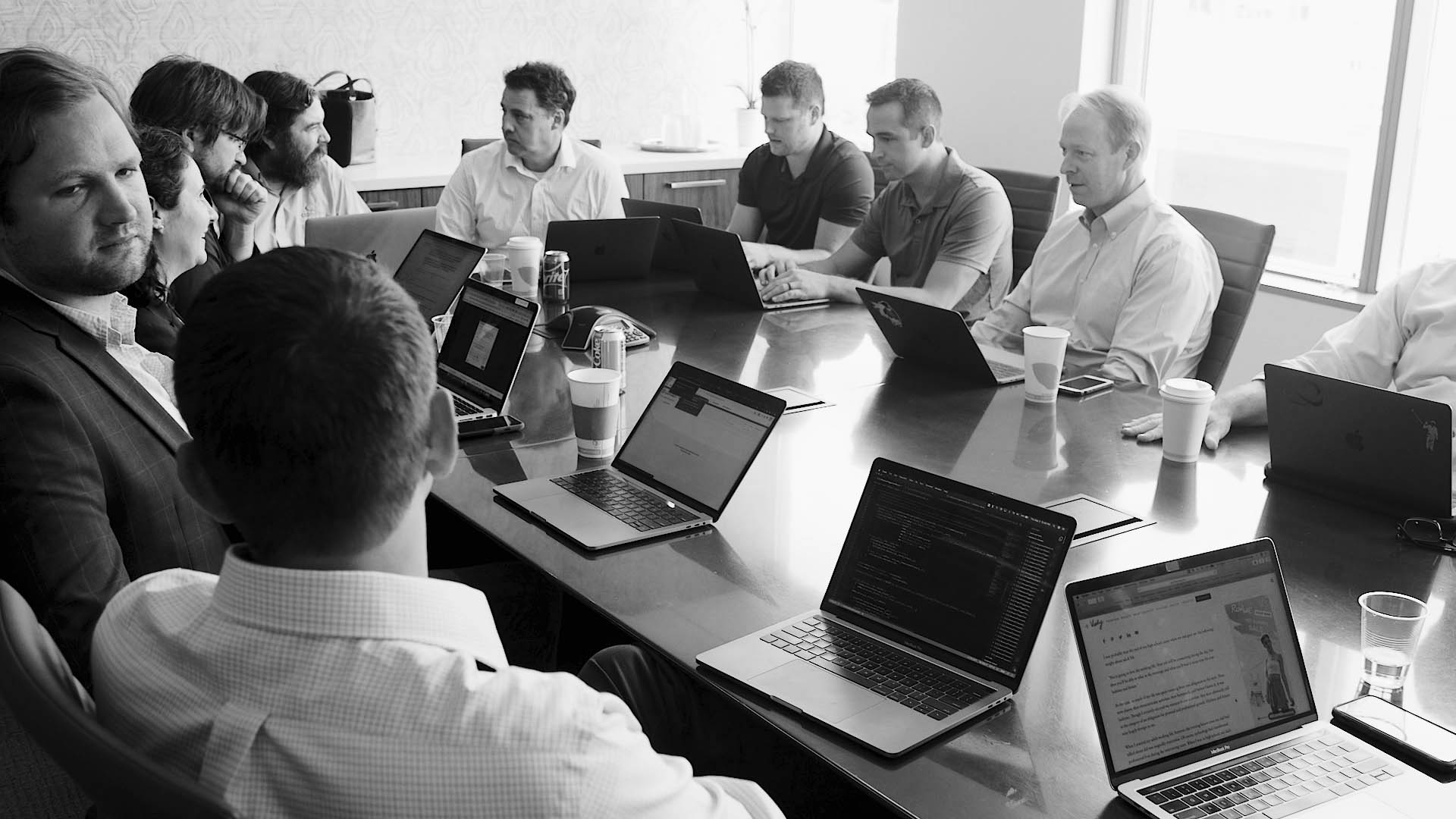 group of men meeting at a conference tab about FinancialForce servicesle