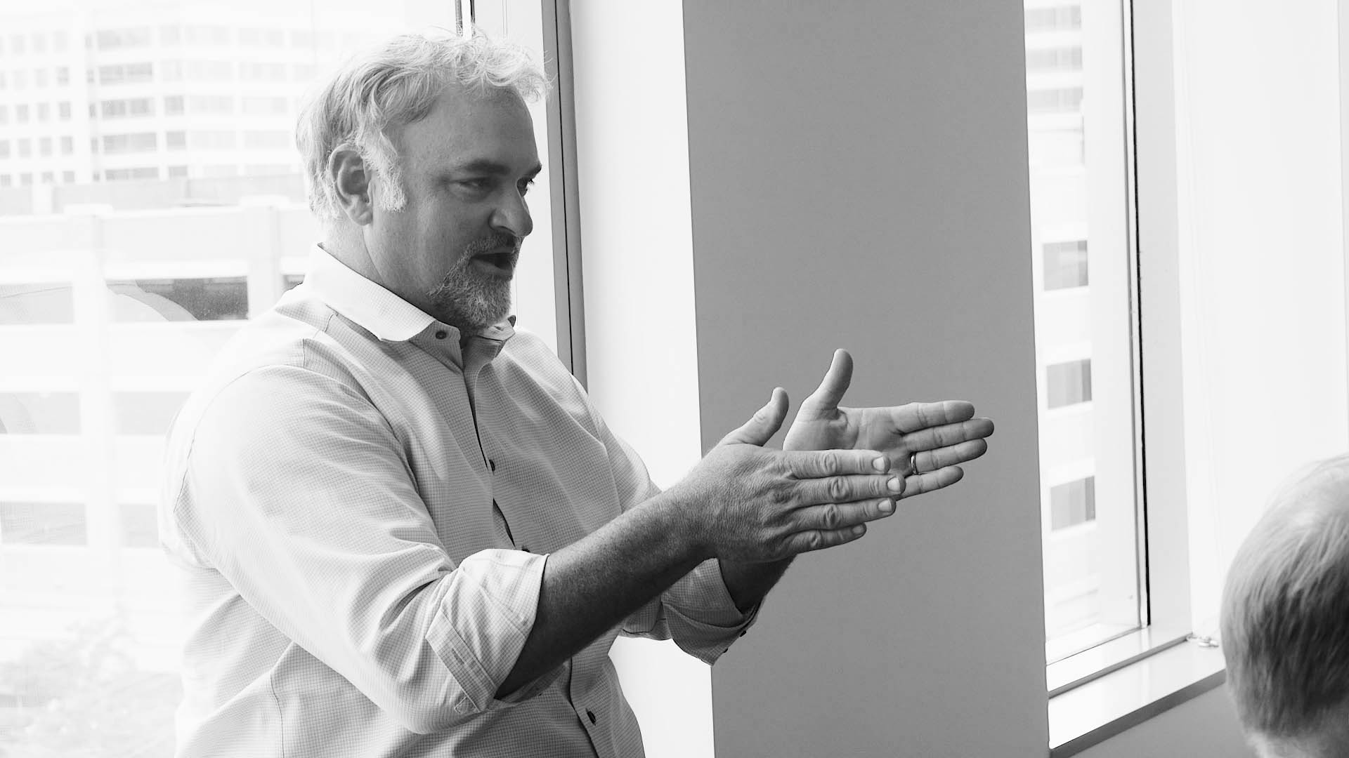 man gesturing with hands at a meeting discussing financialforce erp solutions